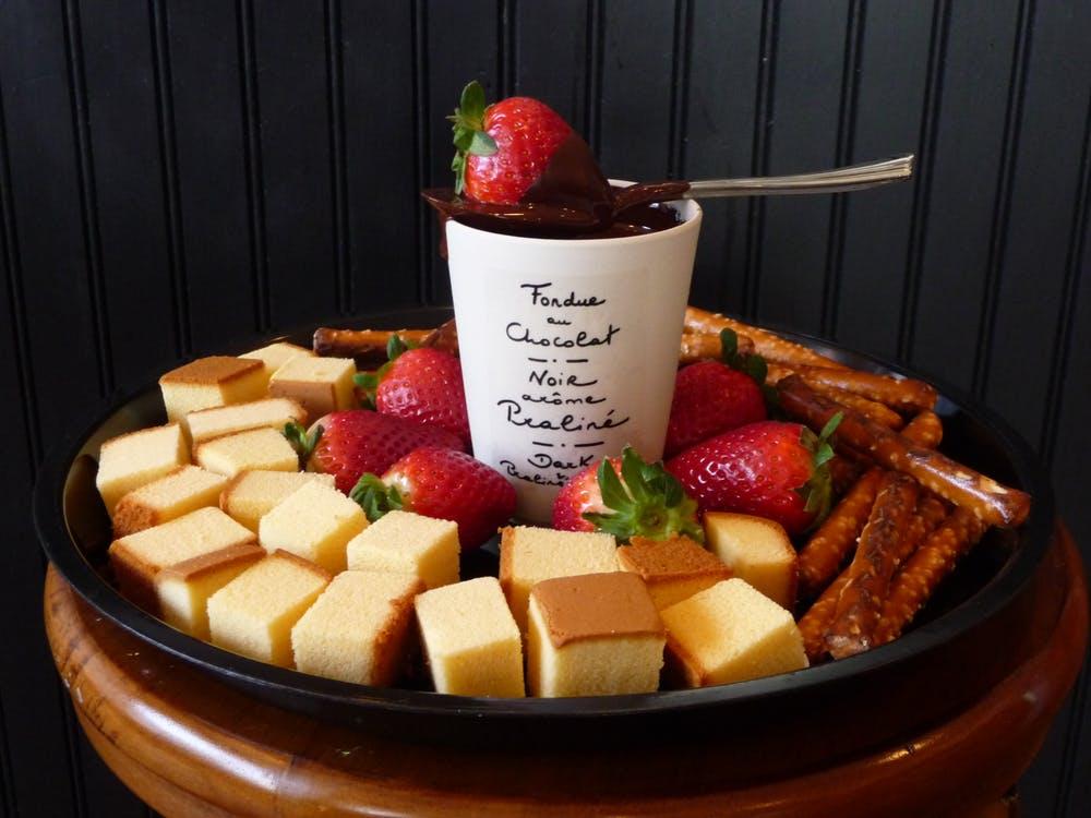 Fondue de chocolate servido no inverno com bolos e morangos.