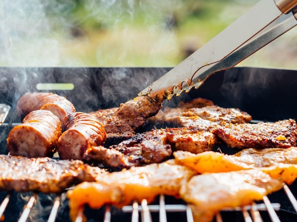 Carne, frango e linguiça sendo grelhados na churrasqueira.