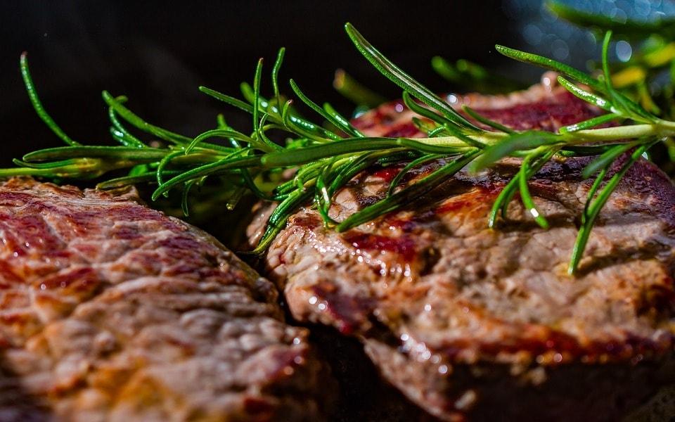 Carne servida com ramo de alecrim em cima,