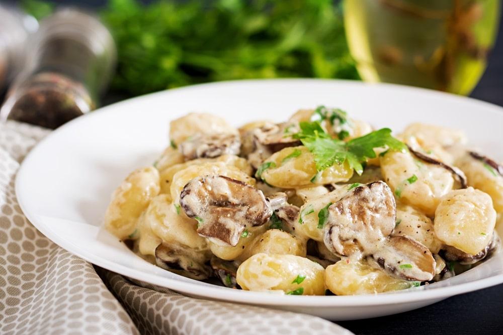 Nhoque ao molho funghi servido na mesa para um jantar de Dia dos Namorados.