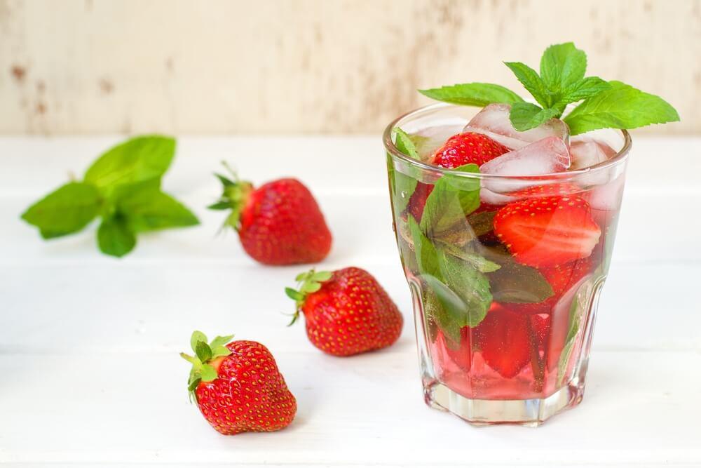 Água saborizada de morango com hortelã servida com gelo em copo de vidro.
