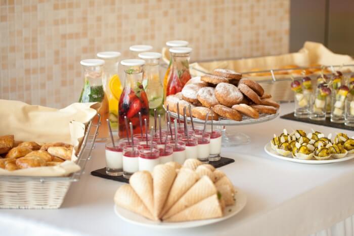Mesa com comidas e bebidas de coffee break corporativo disposta.