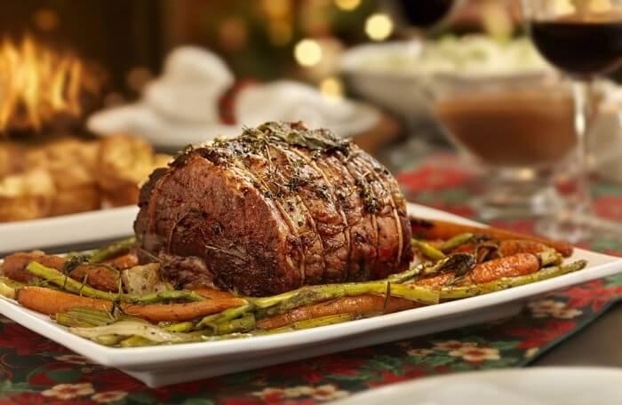 Carne vermelha servida na mesa da ceia de Natal com legumes ao redor.