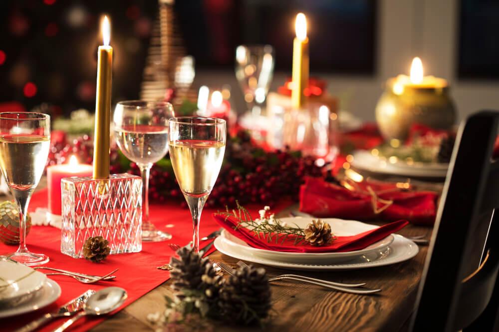 Mesa da ceia de Natal de corada com velas, pratos e taças.