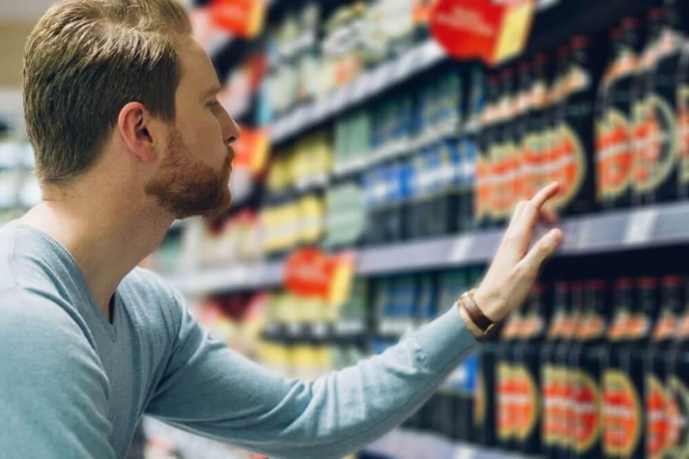 Homem escolhendo a cerveja na prateleira do mercado para churrasco bom e barato.