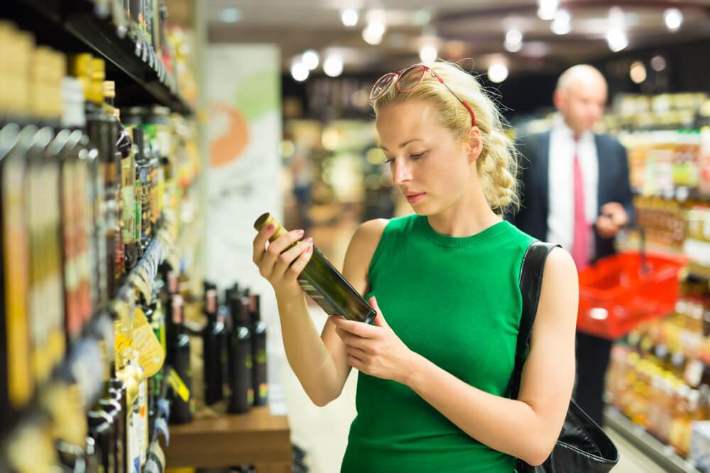 Mulher escolhendo azeite na gôndola do supermercado.