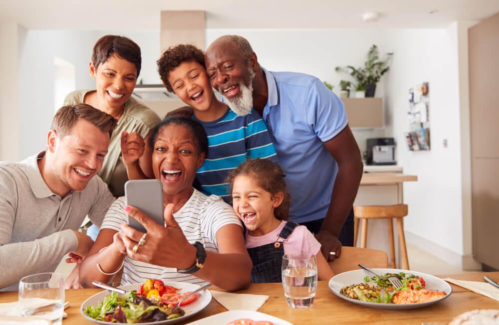 Família reunida na mesa com o que comer no fim de semana servido, como saladas.