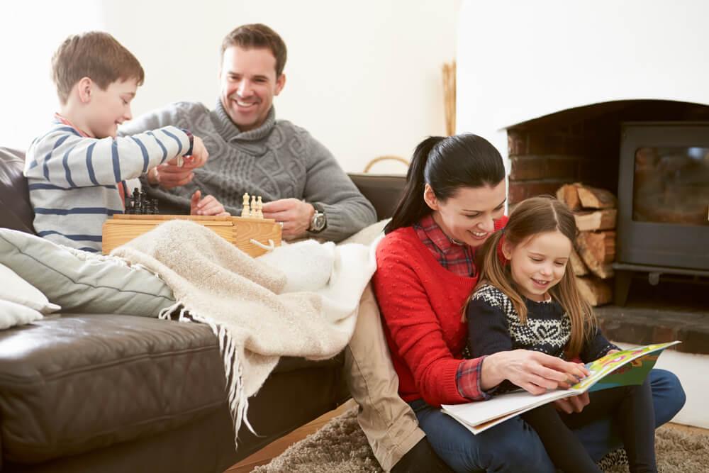 Família com cobertores e livros reunida durante o inverno.
