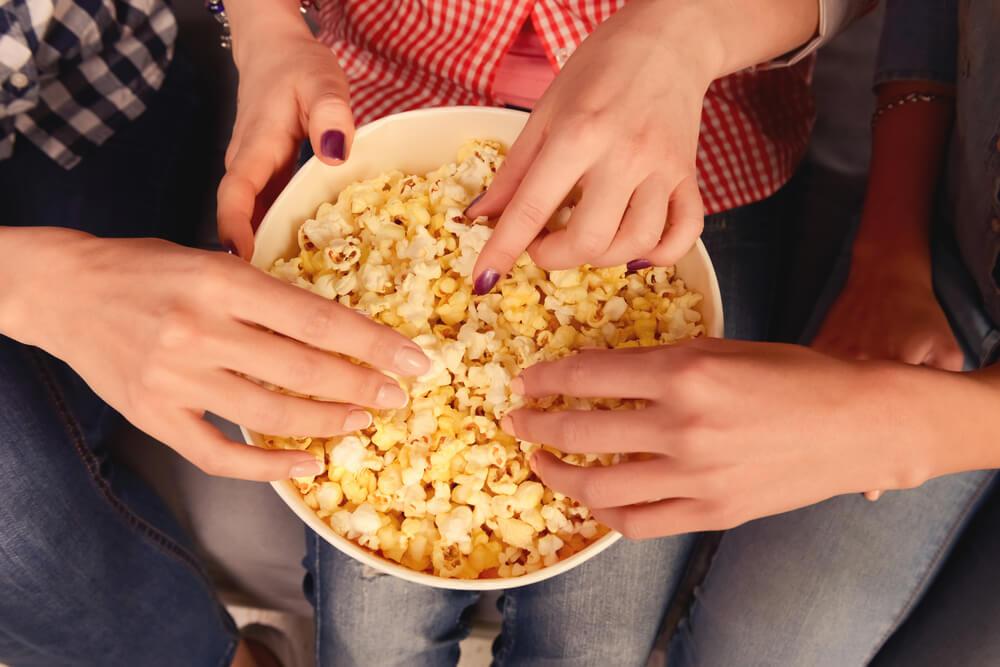 Família comendo pipoca após escolher qual filme ver com os filhos.
