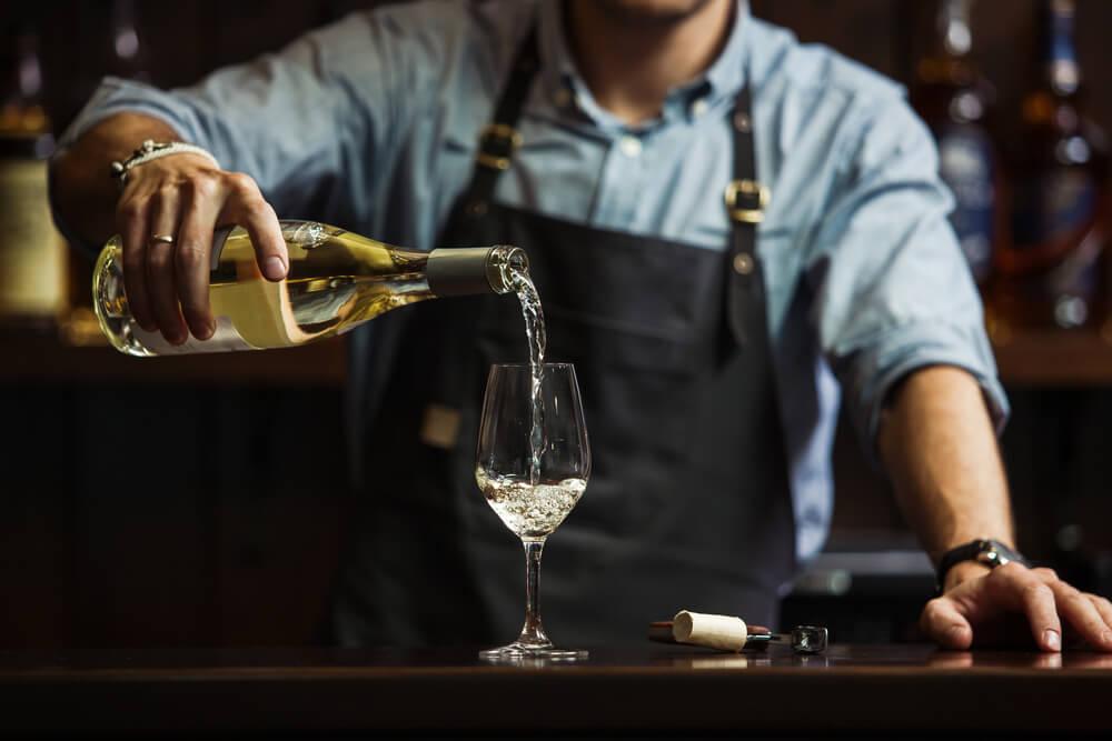 Homem servindo vinho para demonstrar como harmonizar vinho com pratos.