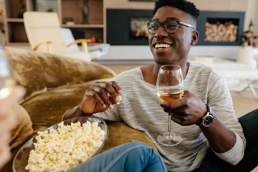 Homem negro com taça de vinho na mão e comendo pipoca durante a noite de jogos.