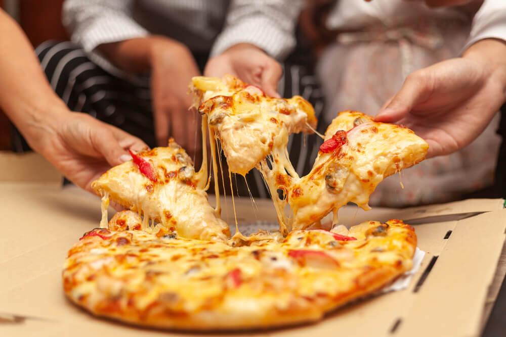 Pessoa pegando fatias de pizza com as mãos durante noite de jogos.