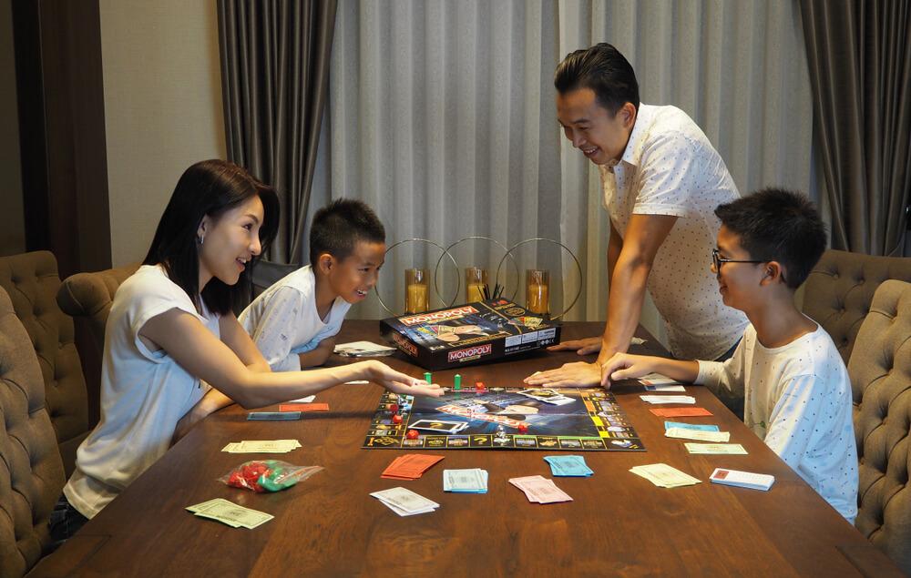 Família na noite de jogos brincando com o jogo de tabuleiro Banco Imobiliário.