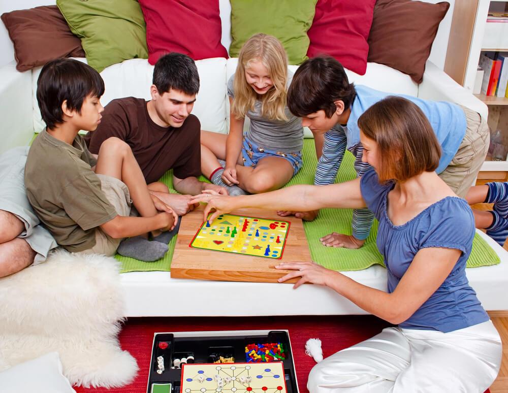 Família com cinco pessoas reunida em cima de um tapete durante a noite de jogos, brincando com jogo de tabuleiro.