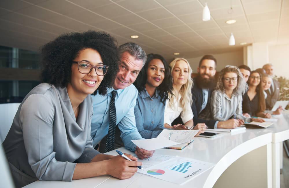 Funcionários sorrindo reunidos em uma mesa de reunião.