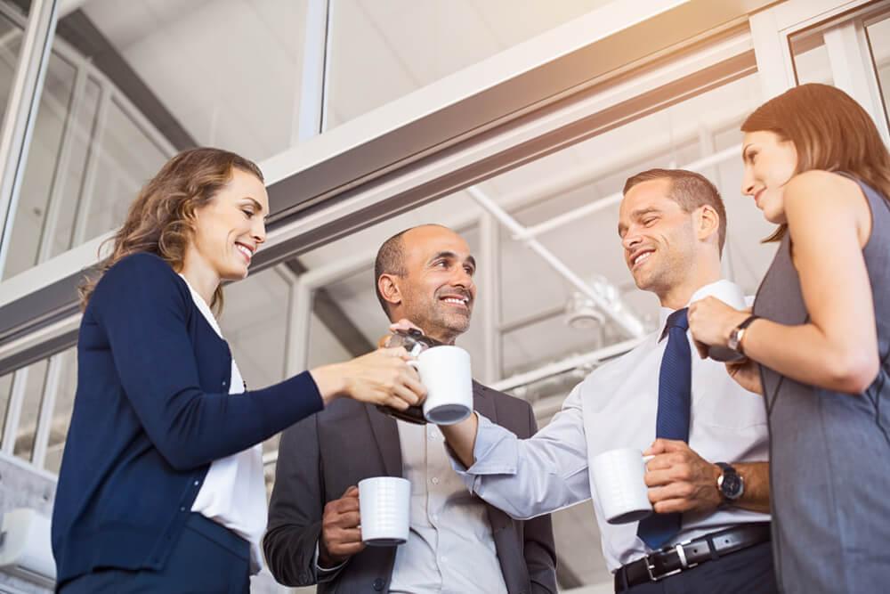 Funcionários bebendo café e conversando durante o coffee break da empresa.