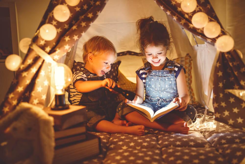 Crianças dentro de uma cabaninha para noite do pijama infantil com luzes e livros.
