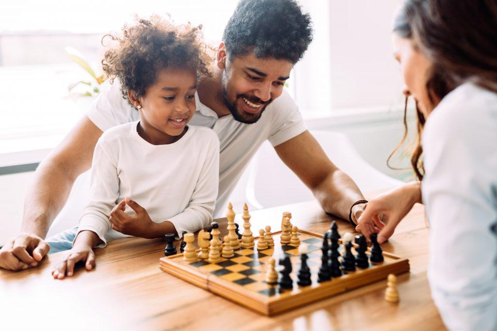 Família de pessoas negras jogando xadrez.