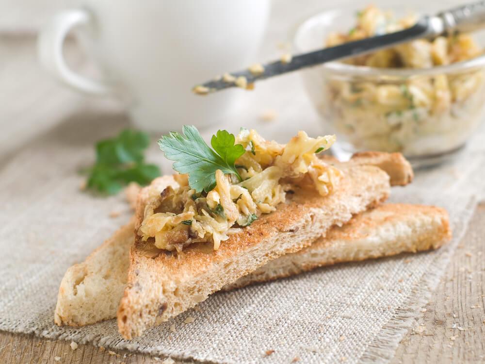 Pão integral com patê de legumes e xícara de café ao fundo.