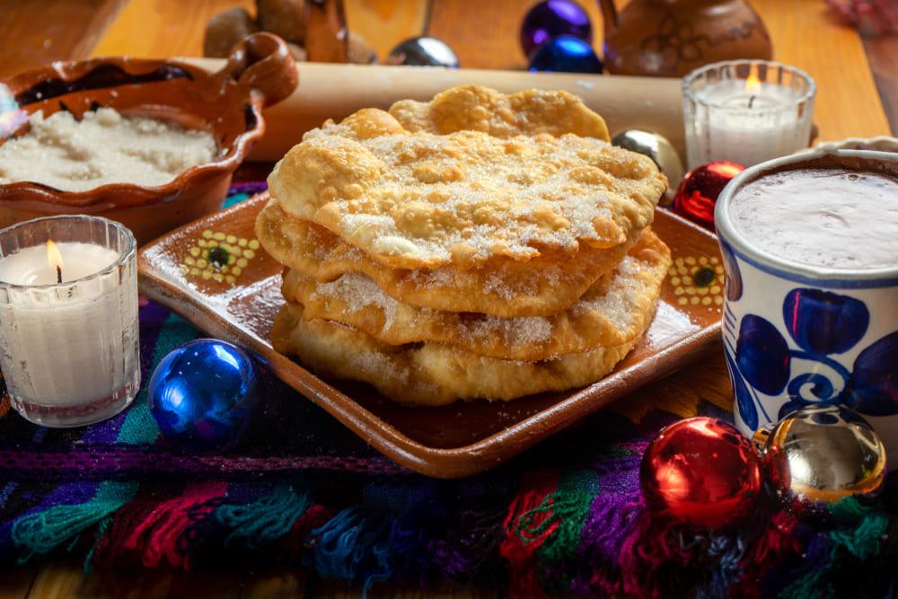 Buñuelos servidos com açúcar por cima.