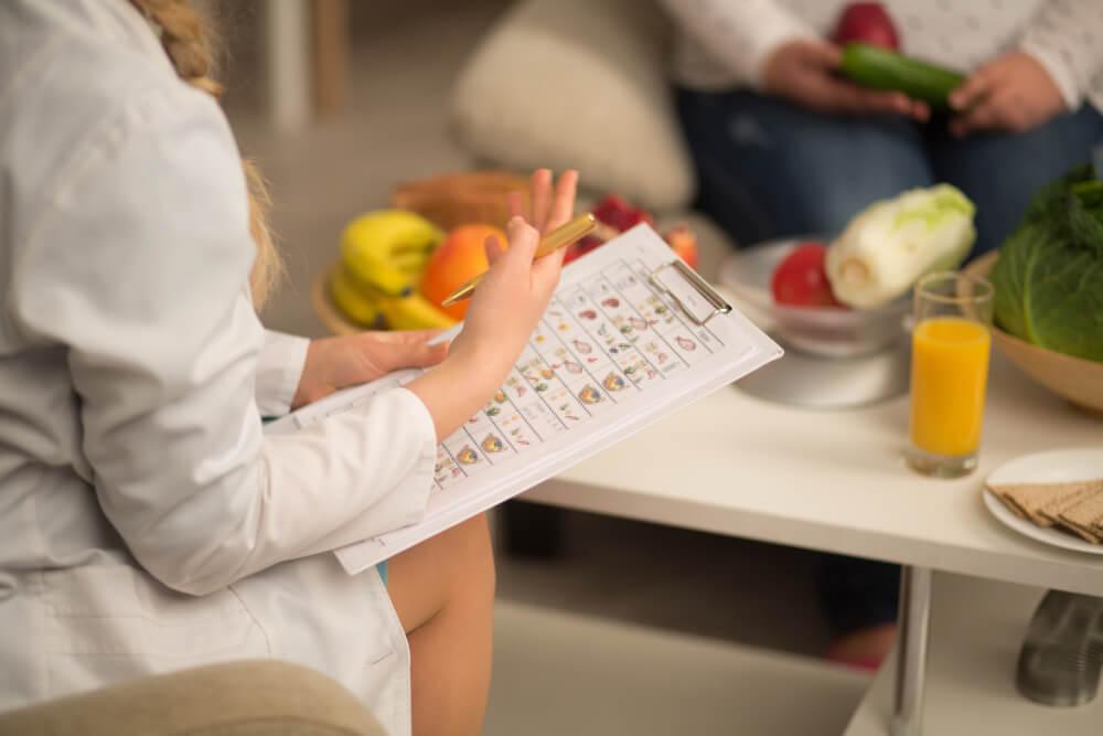 Nutricionista orientando pacientes sobre como ter uma dieta baseada em plantas.