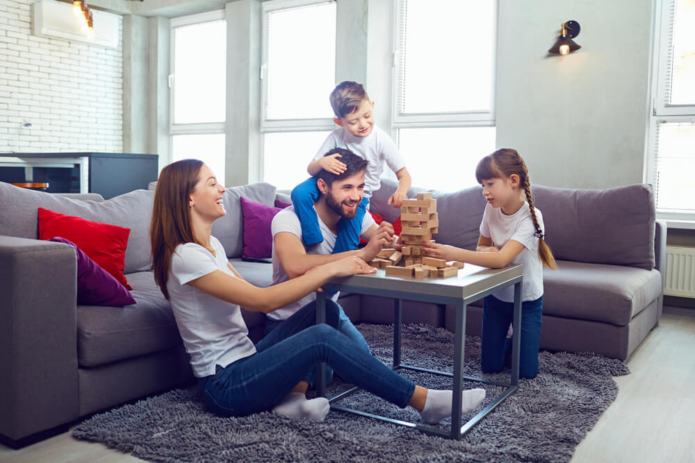 Família reunida na sala, brincando com o jogo Jenga.