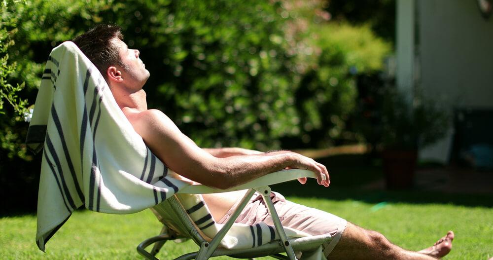 Homem sentado em uma cadeira de praia no jardim, tomando sol.