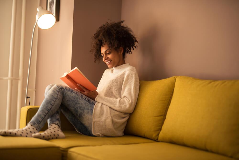 Mulher negra sentada no sofá, lendo um livro.