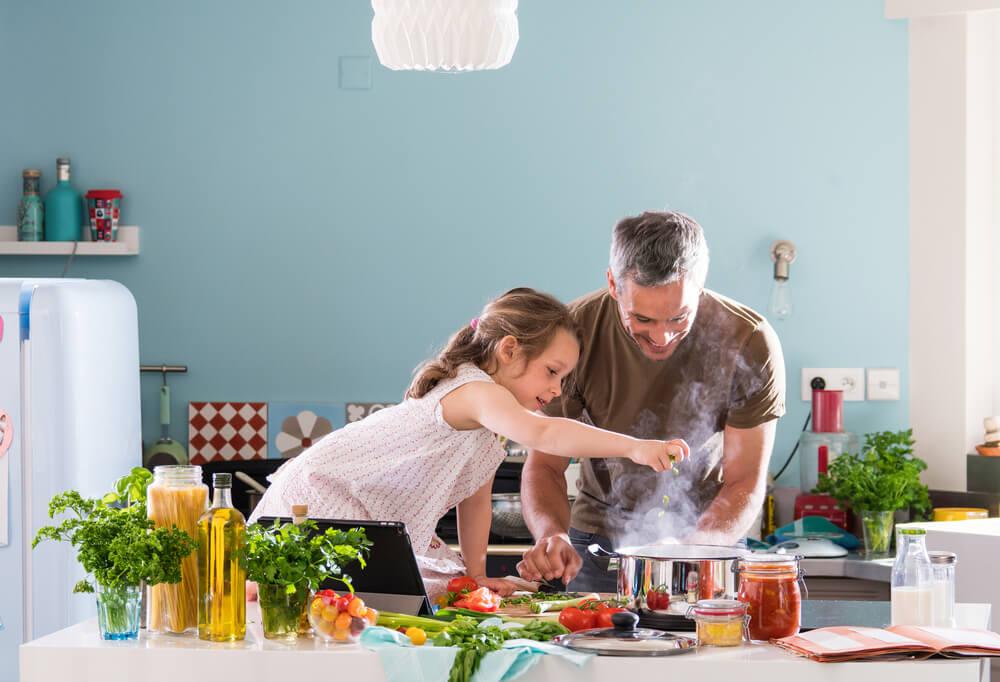 Pai e filha cozinhando juntos durante as férias.