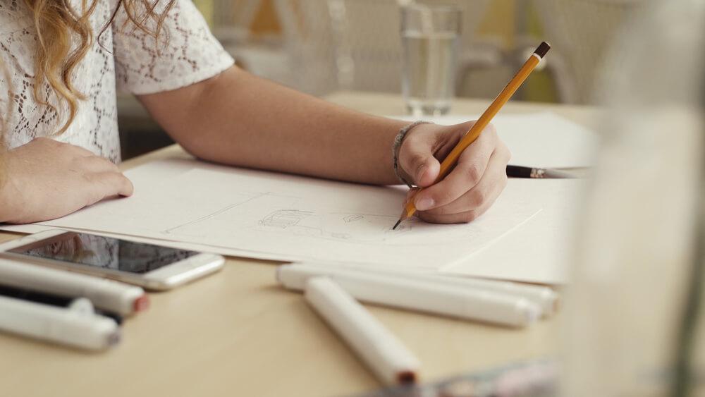 Menina desenhando com um lápis amarelo.