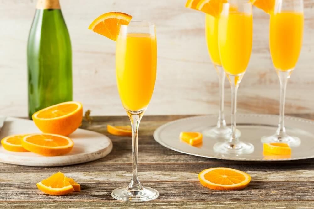 Mesa com quatro taças de champagne com drink mimosa